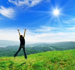 Happy Healthy Woman Jumping towards the sky